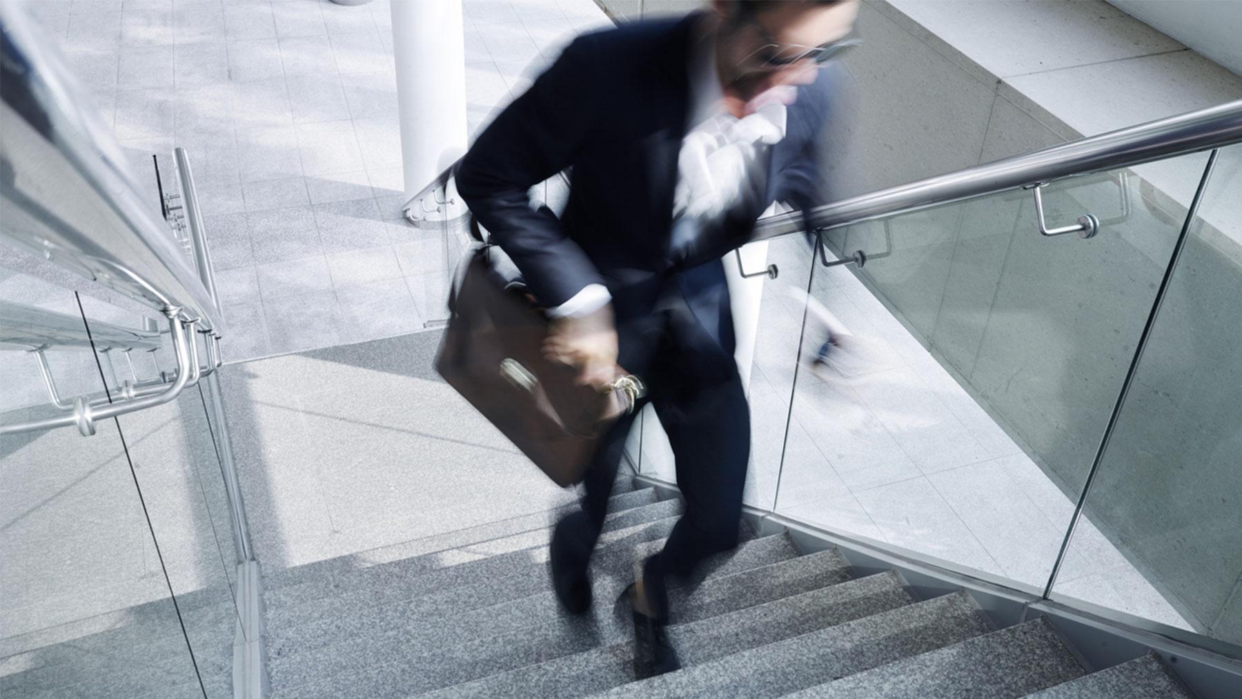 Foto van man in kostuum die een trap oploopt.
