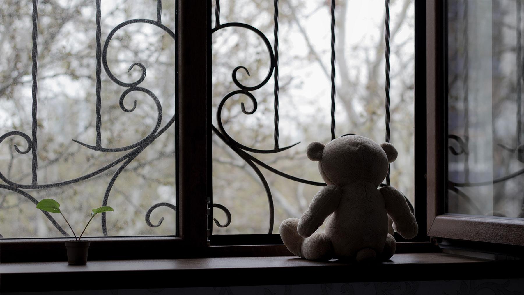 Foto van knuffelbeer die uit een open raam kijkt.