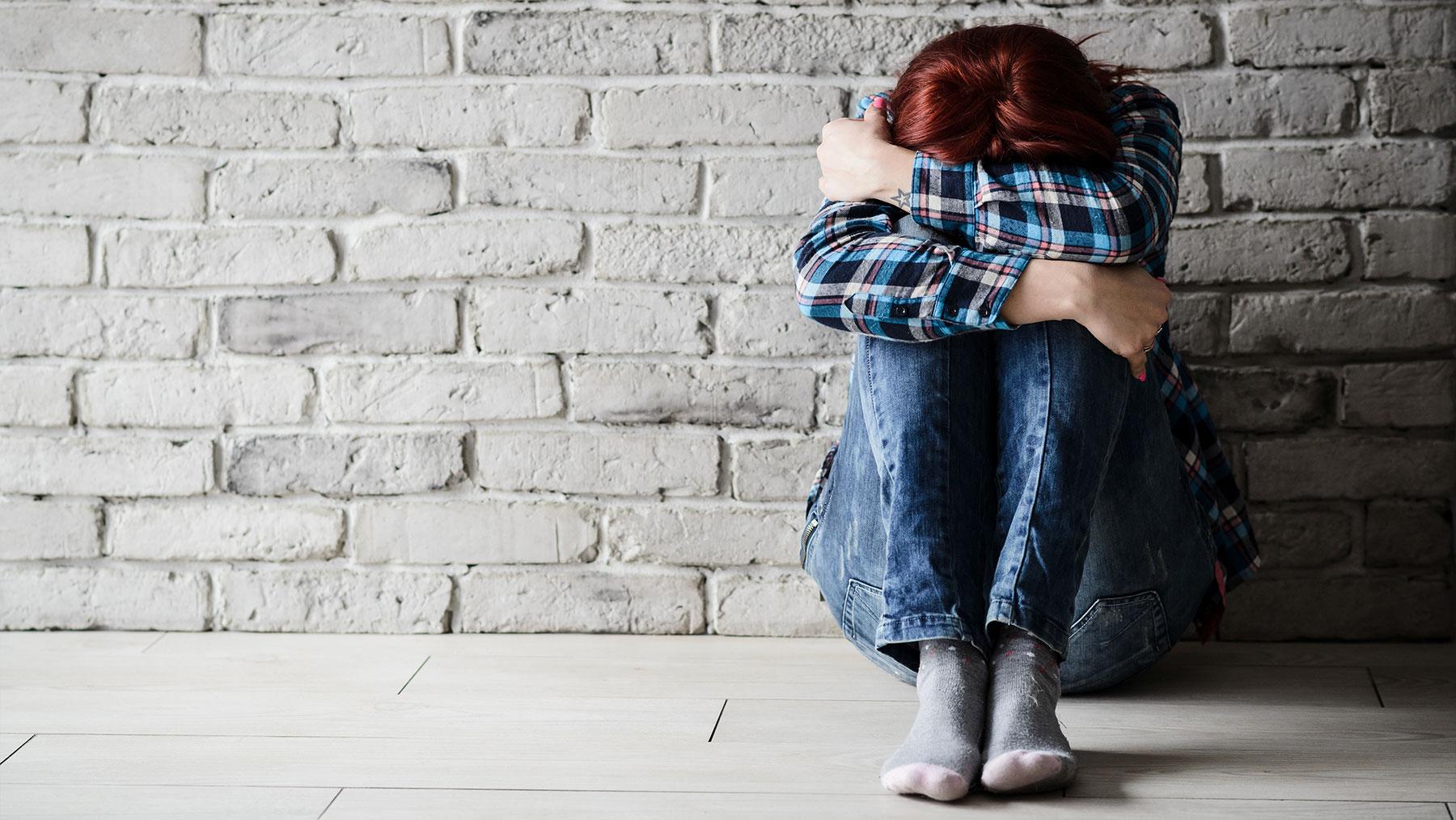 Meisje zit ineengedoken tegen een bakstenen muur.