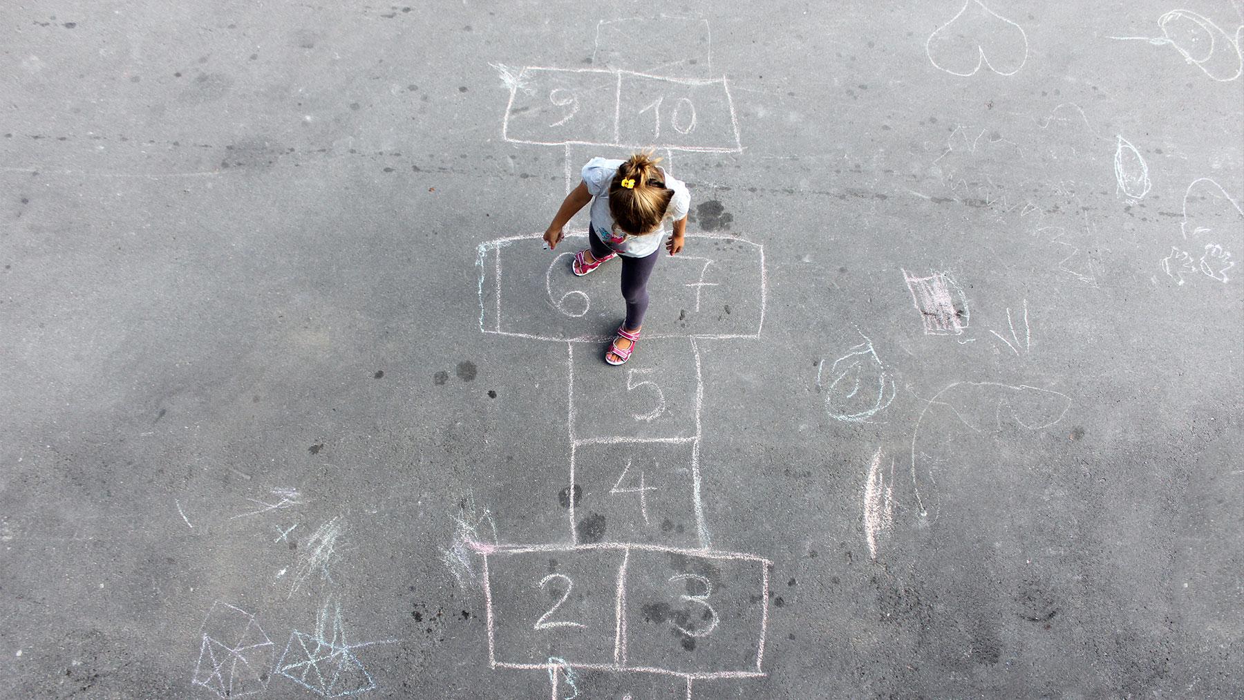 Foto van jong meisje dat aan het spelen is op een in krijt getekend hinkelparcours.