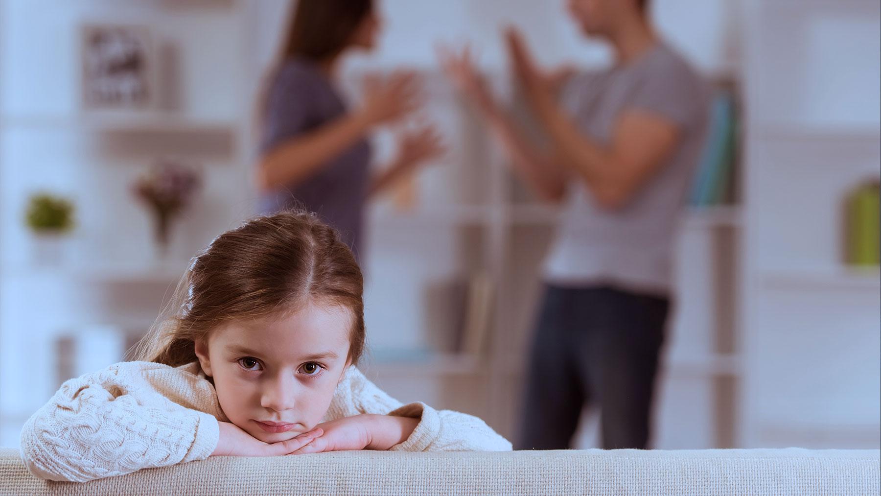 Meisje zit in zetel met ruziënde ouders op de achtergrond.