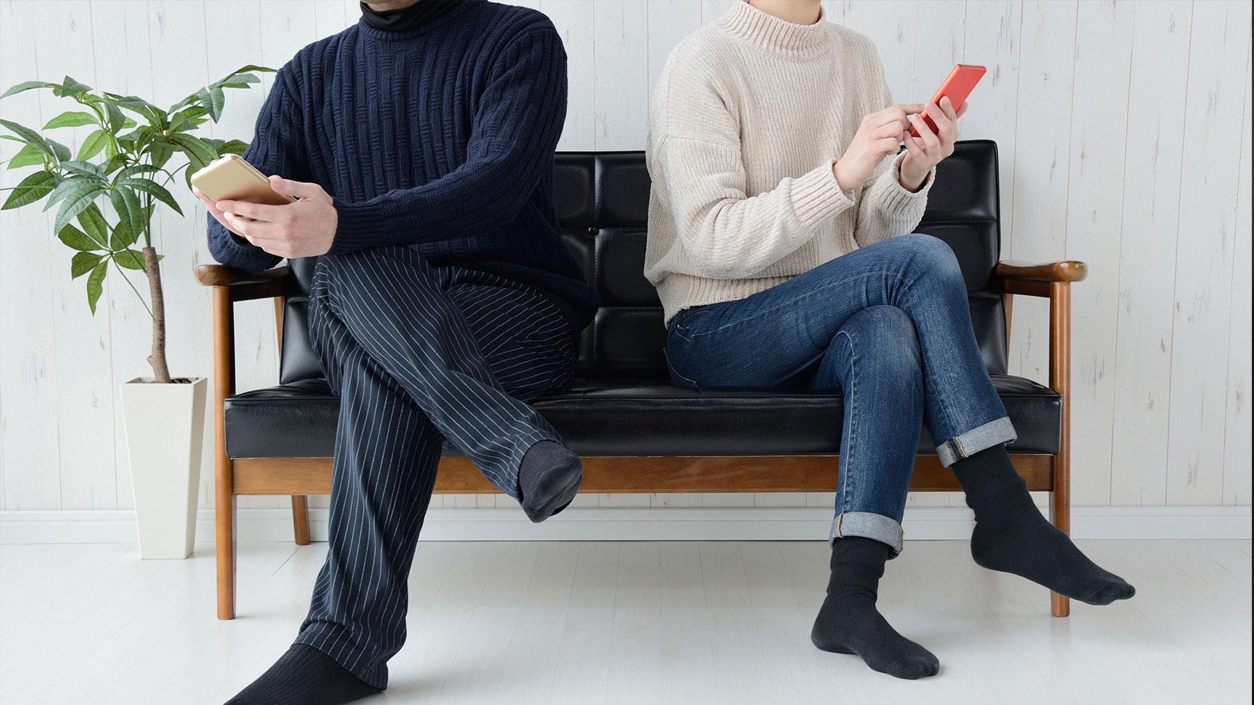 Koppel zittend op een bank. Ze zitten zijdelings en zijn elks op hun gsm bezig.