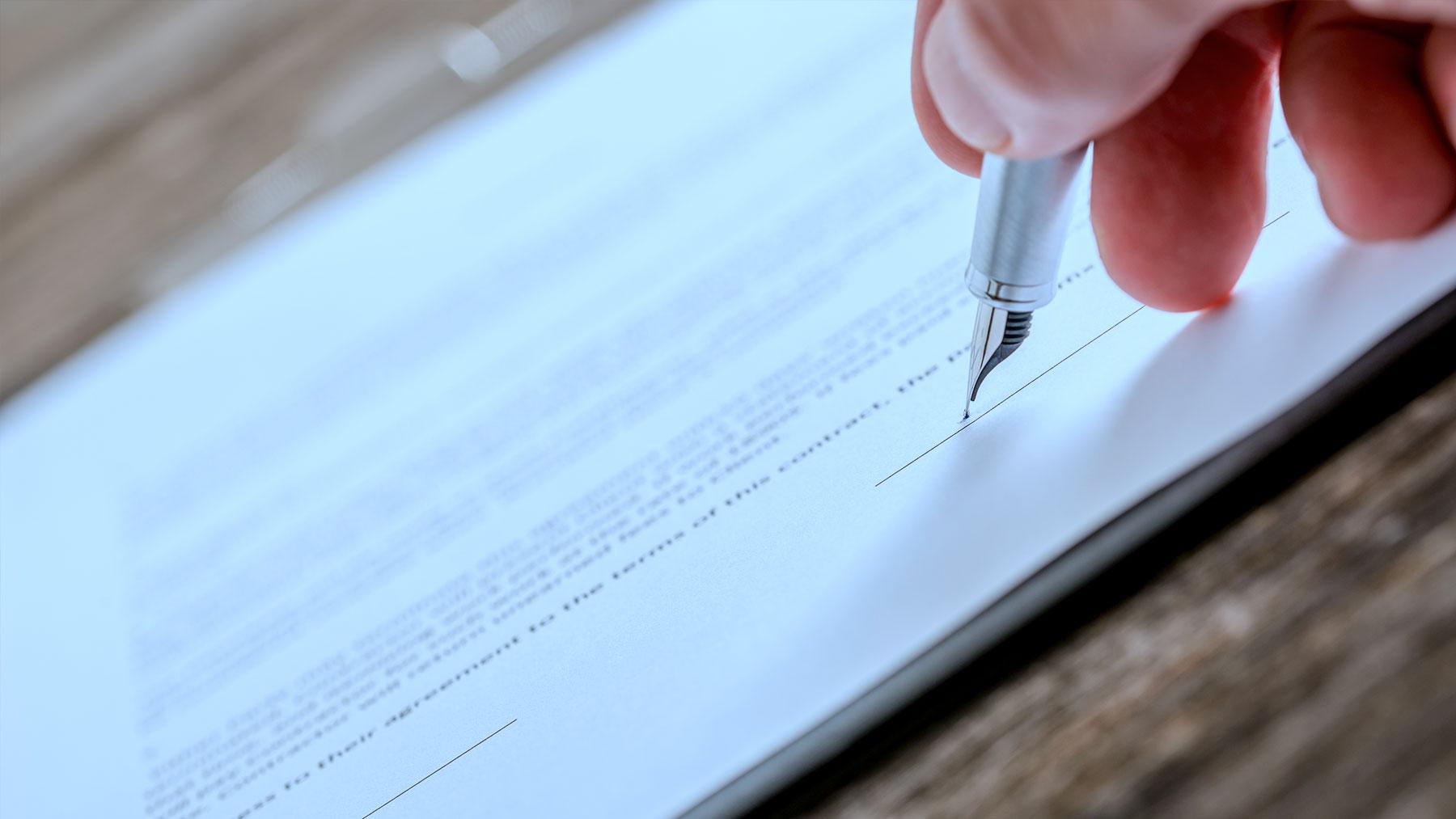 Foto van iemand die met een vulpen een contract ondertekend.