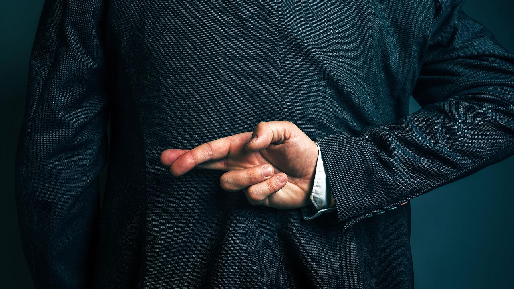 Foto van een persoon in kostuum die achter de rug zijn vingers gekruist houdt.