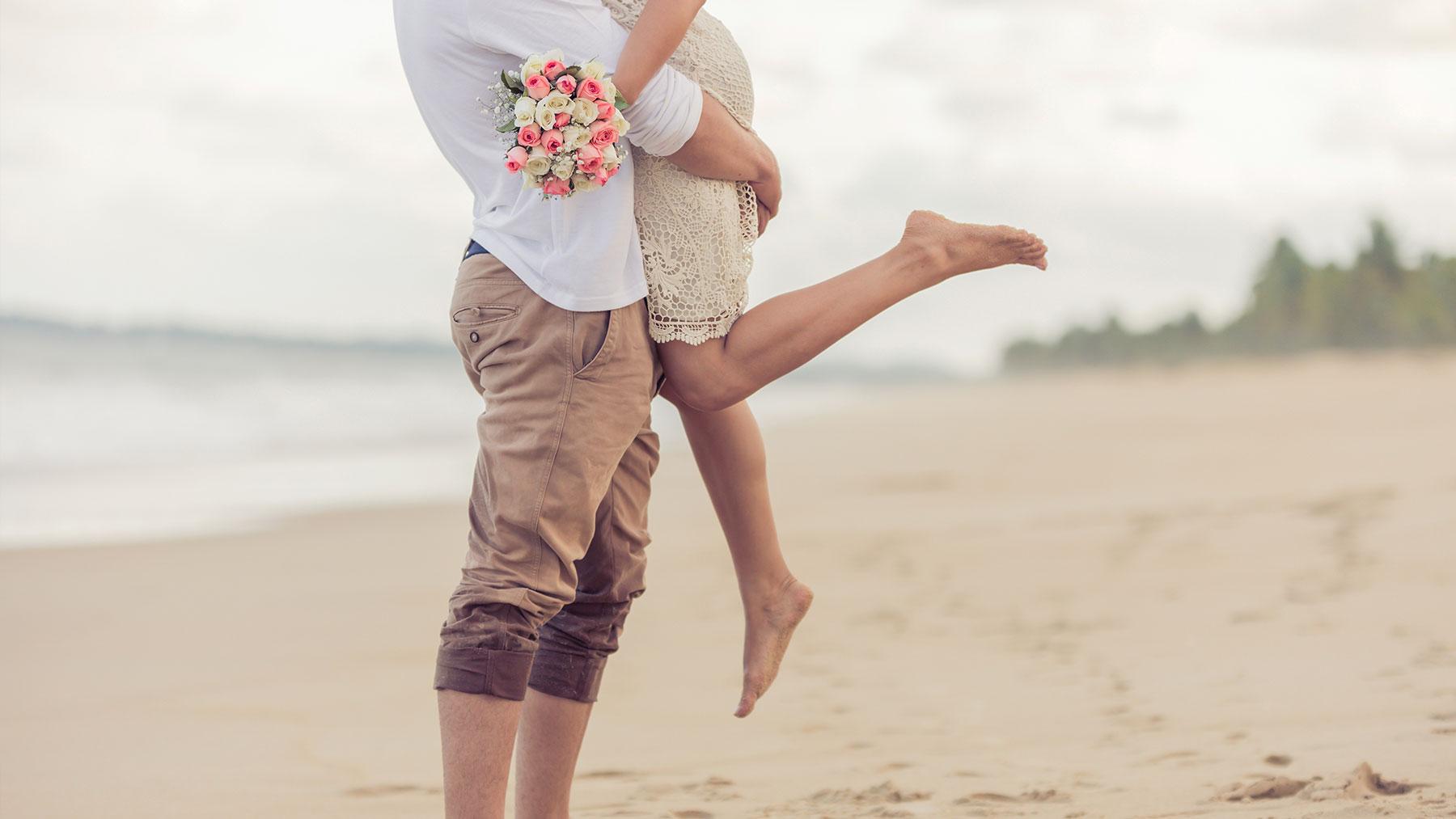 Bruidspaar op het strand. De bruidegom tilt de bruid op.