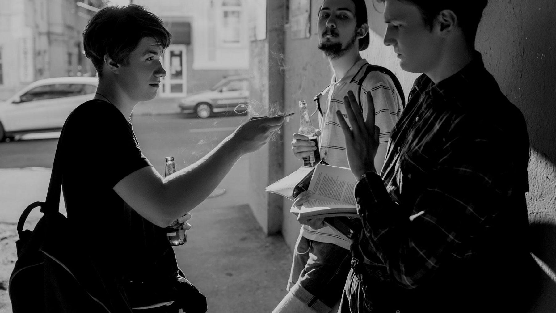 Zwart-wit foto van drie jongens waarvan er twee alcohol drinken en roken. Ze proberen de derde te overhalen om mee te roken.