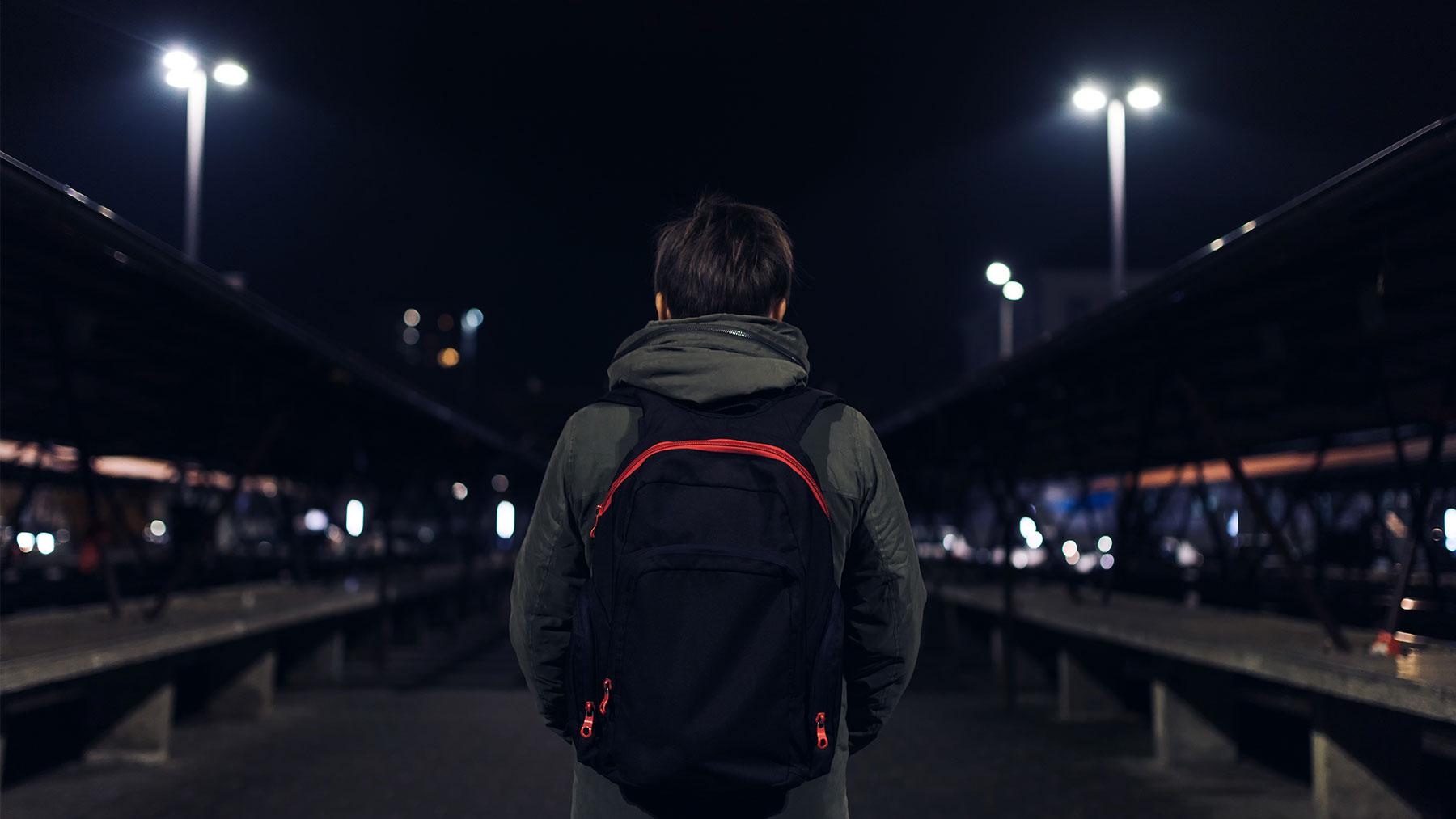 Jongen staat 's nachts met rugzak in een verlaten fietsenstalling.
