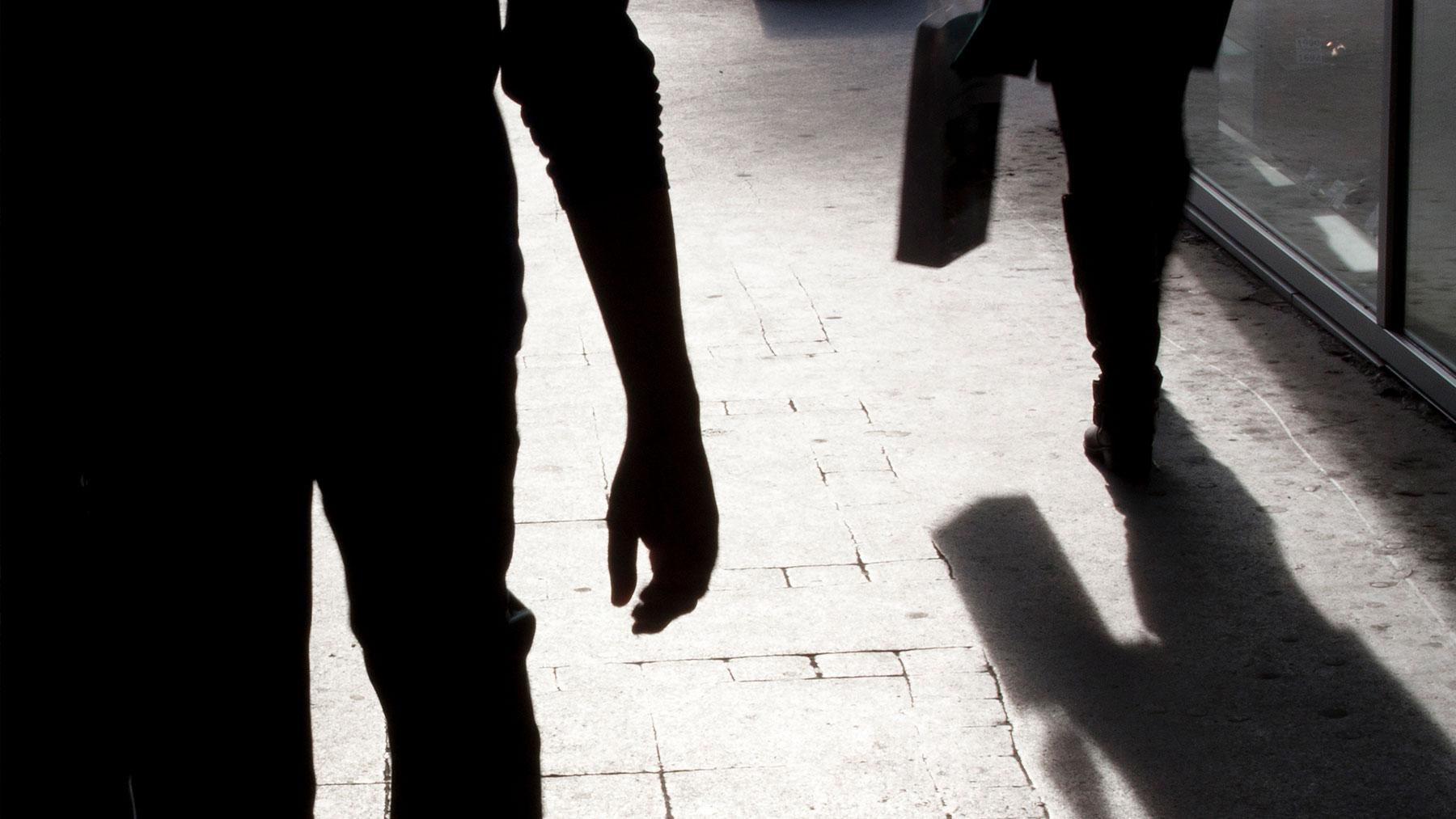 Zwart-wit foto van een persoon die iemand anders schaduwt.