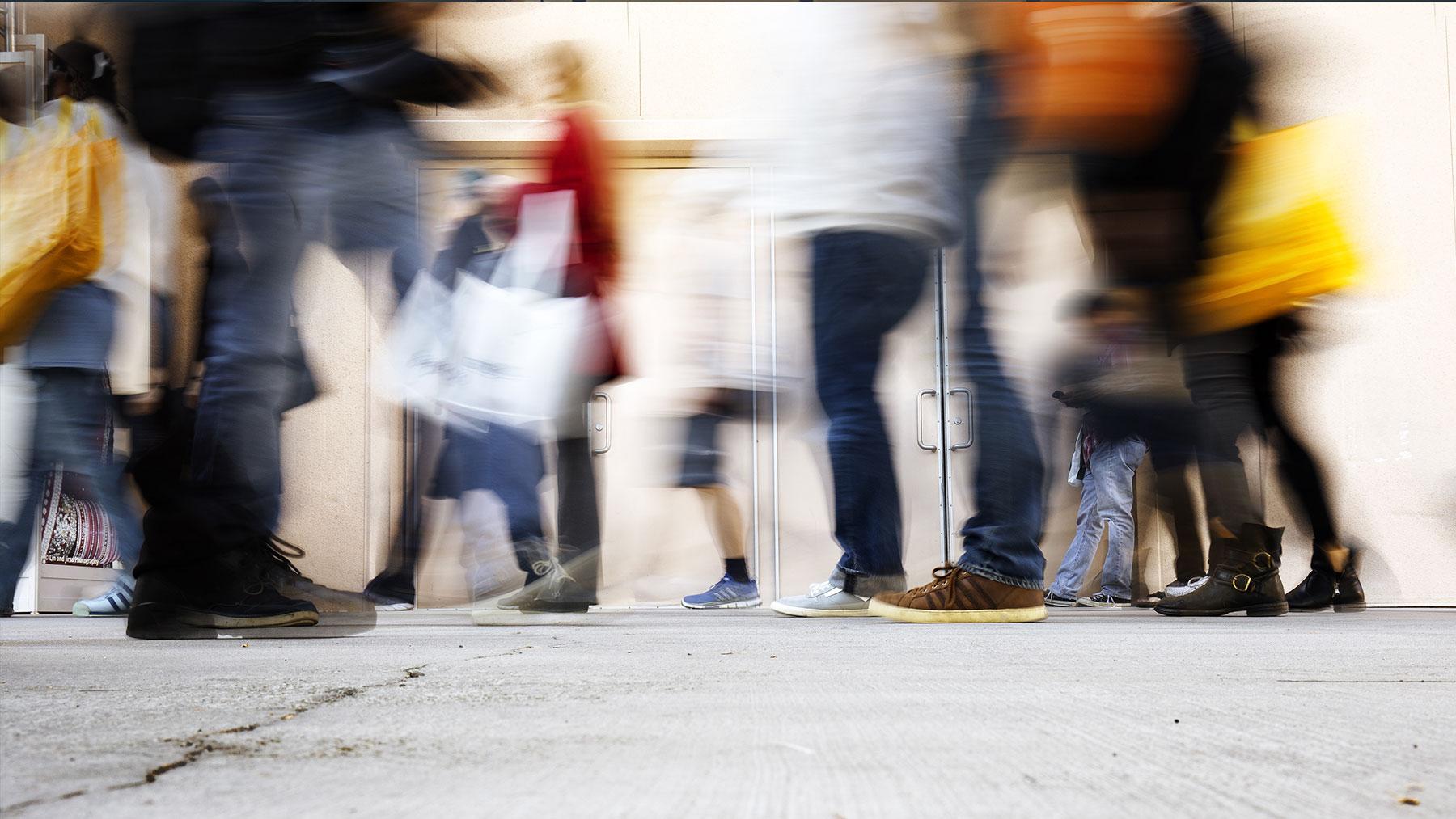 Foto van voorbijgangers in een winkelstraat.