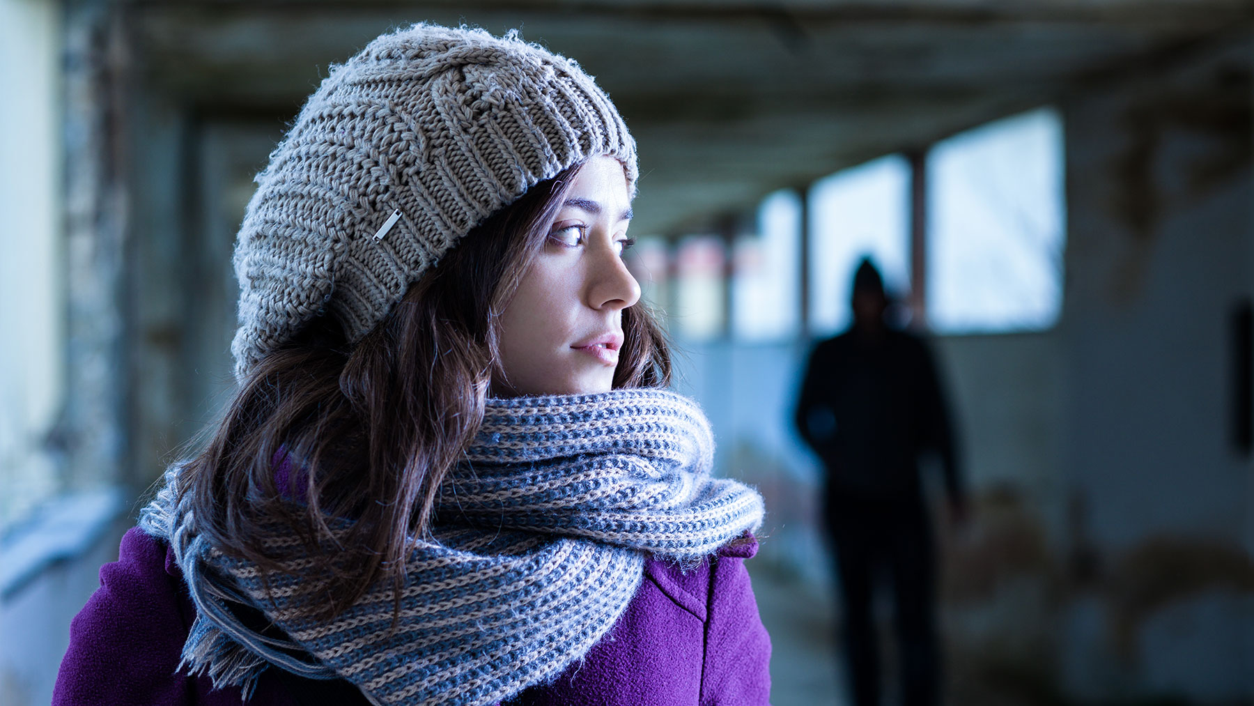 Meisje met muts en sjaal kijkt angstig opzij. Achter haar staat een donker figuur met kap op.