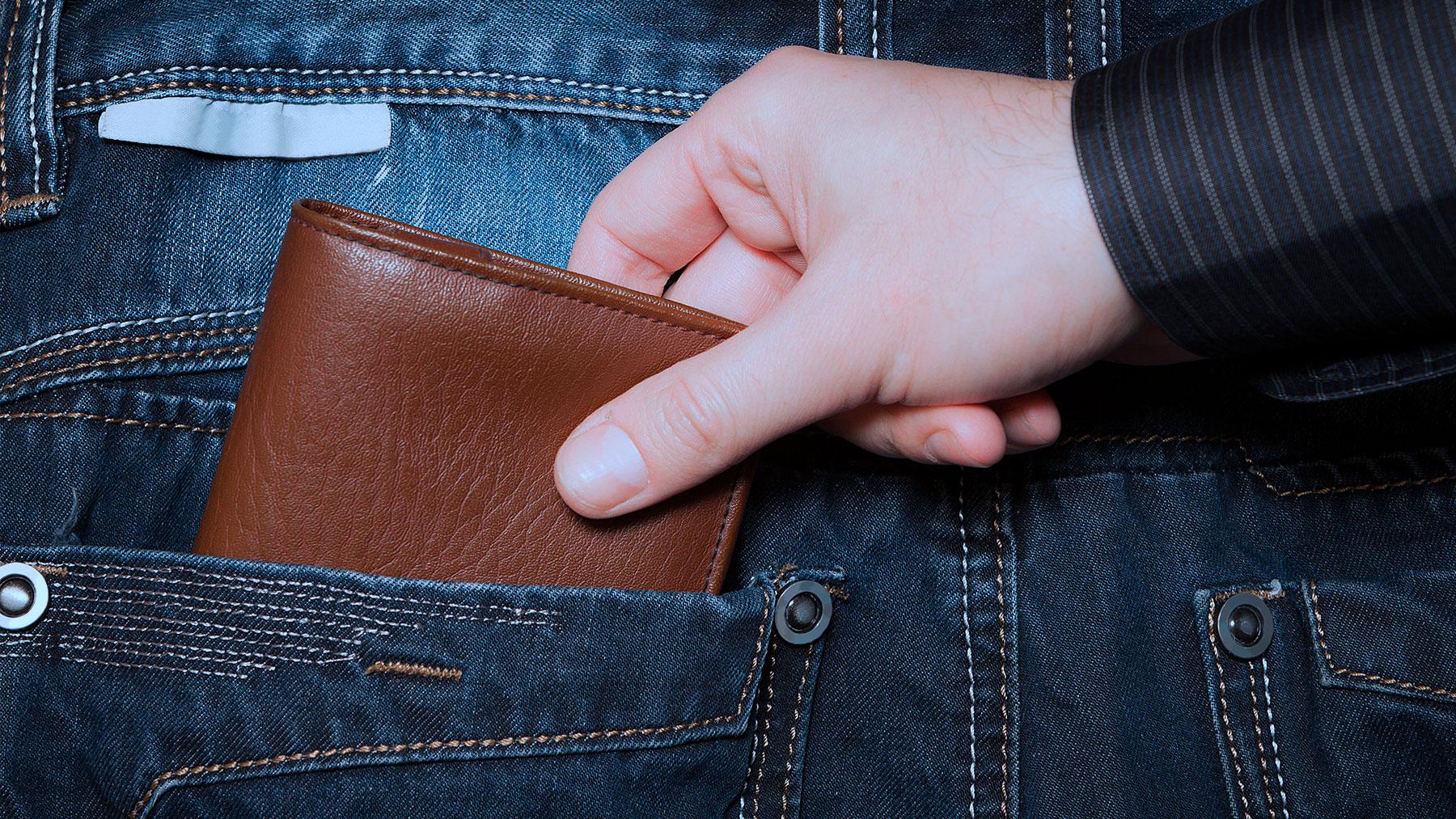 Foto van iemand die een portefeuille uit de achterzak van iemand anders neemt.